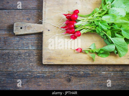 Fresh radishes on a wooden cutting board, over adark  wooden table - Stock Photo