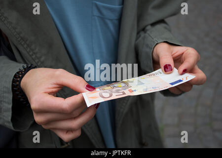 Bruges, Belgium. 8th July, 2017. A woman with painted nails holds a fifty-Euro note. ©AimeeHerd Freelance - Stock Photo