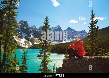 Hiker enjoying the view of Moraine lake in Banff National Park, Alberta, Canada, with snow-covered peaks of canadian - Stock Photo