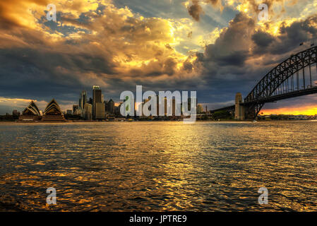 Dramatic sunset sky above Sydney downtown and Harbour Bridge in Australia.