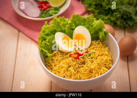 Instant noodles in bowl with vegetables and  boiled egg on wood background - Stock Photo