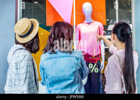 young hipster girls looking at showcase in shopping mall, friends shopping concept - Stock Photo