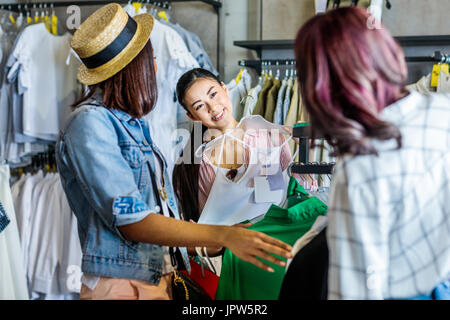 multicultural hipster girls choosing clothes in boutique, fashion shopping girls concept    - Stock Photo