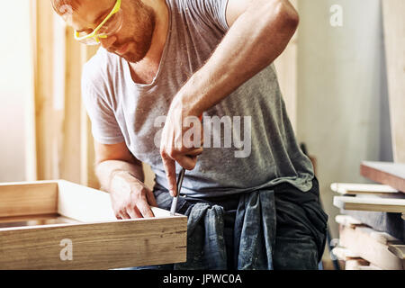 A dark-haired man with a beard and protective green glasses treating a wooden product with a chisel in the workshop - Stock Photo