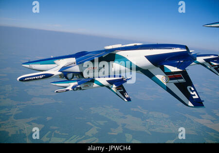 Russian AirForce Team Rus Aero Vodochody L-39 Albatross formation flying inverted over green fields and forests - Stock Photo