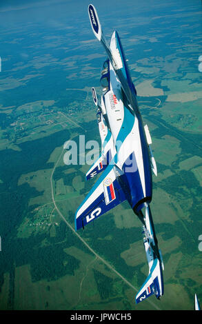 Russian AirForce Team Rus Aero Vodochody L-39 Albatross formation in a knife-edge climbing turn over green fields and forests