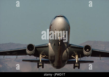 Sun Country Airlines McDonnell Douglas DC-10-10 taking-off with hills behind - Stock Photo