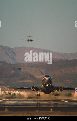 American Airlines McDonnell Douglas DC-10-10 taking-off with a Boeing 727 on final-approach and hills behind - Stock Photo
