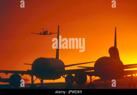 Boeing 757 and Lockheed L1011 Tristar queue on taxiway with Embraer EMB-120 Brasilia taking-off behind at dusk - Stock Photo