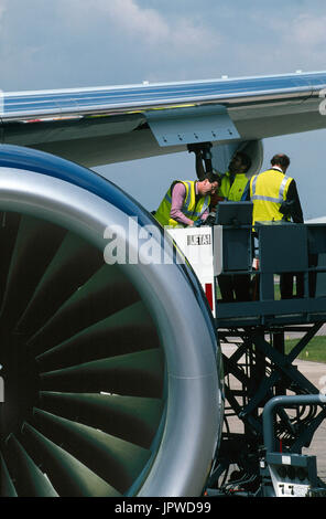 refuellers wearing yellow high-viz tabards standing on a cherry-picker attaching a fuel-hose to the underside of - Stock Photo