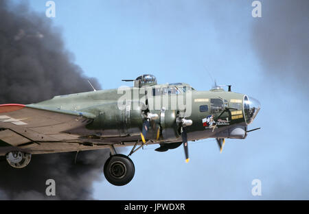 USAF Boeing B-17G Flying Fortress named 'Texas Raiders' taking-off through a cloud of black smoke with undercarriage - Stock Photo