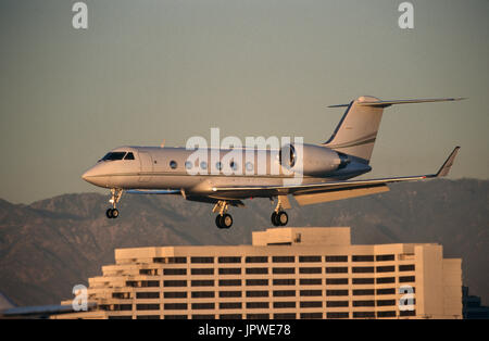 Gulfstream 400 on final-approach with flaps deployed and a hotel behind - Stock Photo