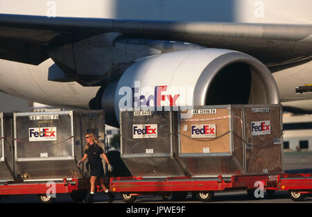 LD3 containers being loaded onto trolleys with a GE CF6-80 engine-intake of a FedEx Airbus A300-600 freighter behind - Stock Photo