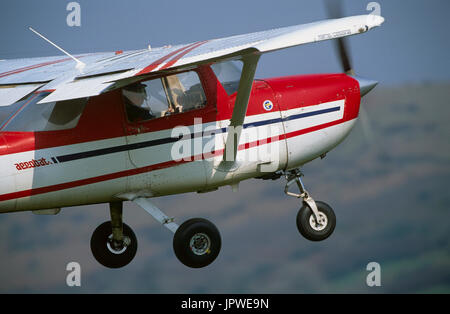 Cessna 150m FRA150M climbing out after take-off with flaps deployed and hills behind - Stock Photo