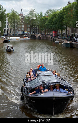 A boat full of tourists travels along a canal in Amsterdam, Holland. - Stock Photo