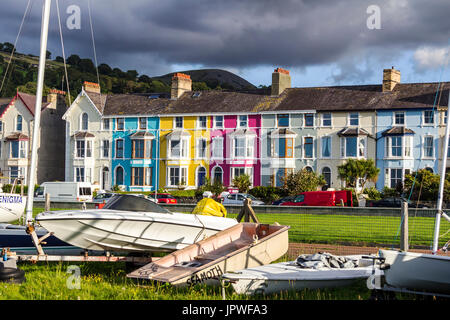 A view of Llanfairfechan with their colourful houses on the seafront with boats on the side.  The image was taken - Stock Photo
