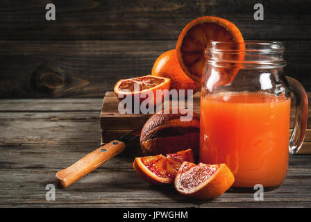 Refreshing summer drink. Juice from red Sicilian oranges. On a rustic wooden table, with whole and cut oranges. - Stock Photo