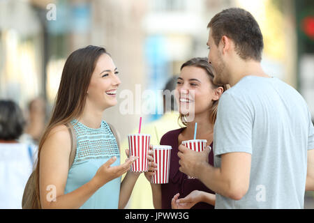 Three happy friends talking and holding refreshments in the street - Stock Photo