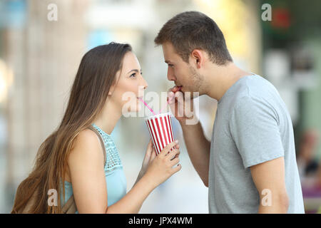 Side view portrait of a happy couple sharing a takeaway refreshment in the street - Stock Photo