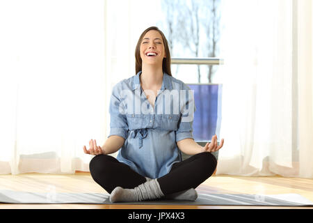 Front view portrait of a happy pregnant woman practicing yoga exercises on the floor at home - Stock Photo
