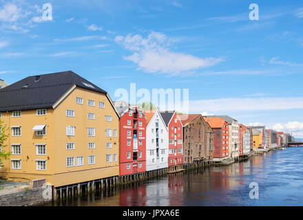 Colourful historic wooden warehouse buildings on stilts on River Nidelva waterfront in old town in summer. Trondheim - Stock Photo