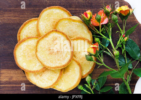 Home food plate with pancakes on a wooden board with a rose flower - Stock Photo