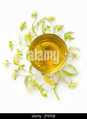 Tea from linden flowers with inflorescences of lindens around a cup on a white background. Top view. Vertical photo - Stock Photo