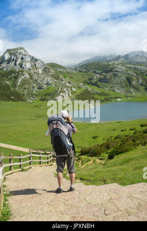 Family trip to Spain nature: father with a baby in a backpack hiking on the trail to high mountain lakes in sunny - Stock Photo