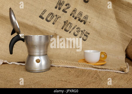 Tavigliano, Italy - August, 01, 2017: Front frame to Italian moka and coffee beans into the cup. Vintage still life - Stock Photo