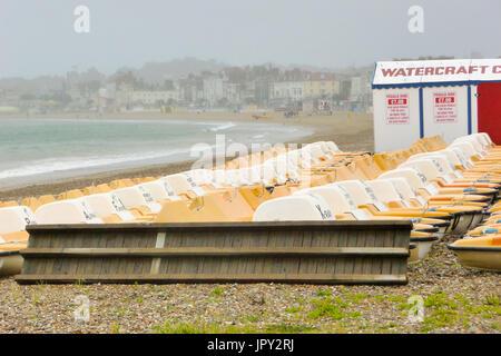 Weymouth, UK. 2nd Aug, 2017. Piles of pedalos lie, unused, on rainy Weymouth sands Credit: stuart fretwell/Alamy - Stock Photo