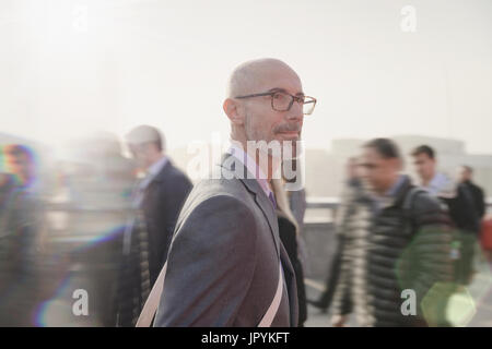 Serious, pensive businessman walking on busy urban pedestrian bridge - Stock Photo