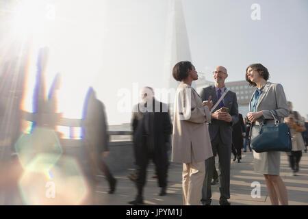 Business people talking on sunny, urban pedestrian bridge, London, UK - Stock Photo