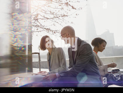 Businessman and businesswoman talking, meeting in sunny urban park - Stock Photo