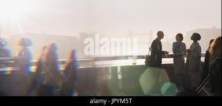 Silhouette business people talking on sunny urban bridge, London, UK - Stock Photo
