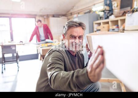 Smiling male carpenter examining wood boat in workshop - Stock Photo