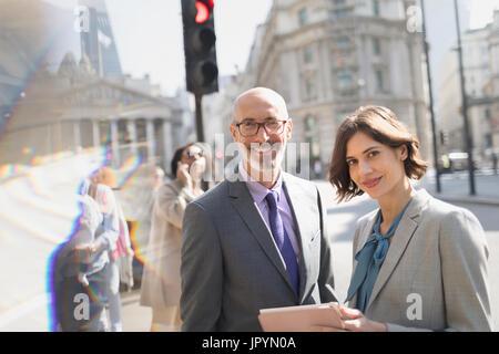 Portrait smiling, confident business people using digital tablet on sunny urban city street, London, UK - Stock Photo