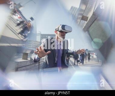 Businessman using virtual reality simulator glasses on urban bridge - Stock Photo