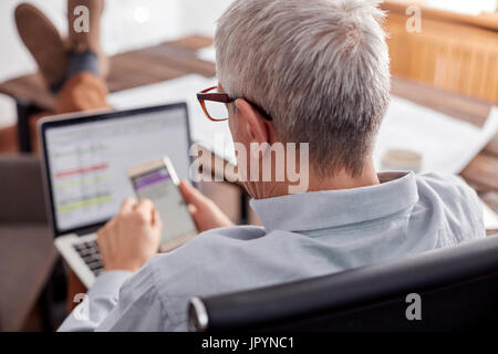 Businessman working, using cell phone and laptop in office - Stock Photo