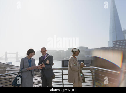Business people using digital tablet at sunny urban waterfront, London, UK - Stock Photo