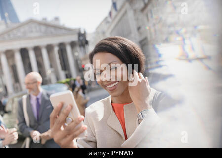 Smiling businesswoman taking selfie with camera phone, London, UK - Stock Photo
