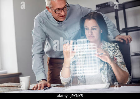 Female architect performing telekinesis, hovering futuristic glowing plastic model - Stock Photo