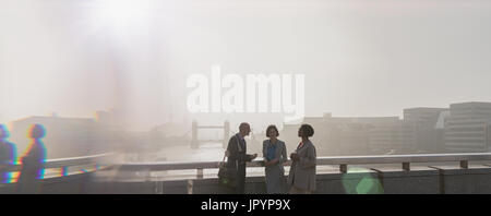 Silhouette business people on sunny urban city bridge over Thames River, London, UK - Stock Photo