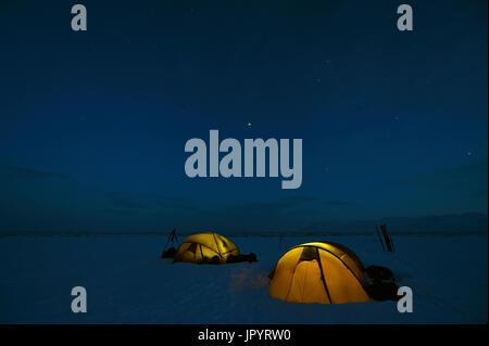Lit tents at night - Agardbukta Spitzberg - Stock Photo