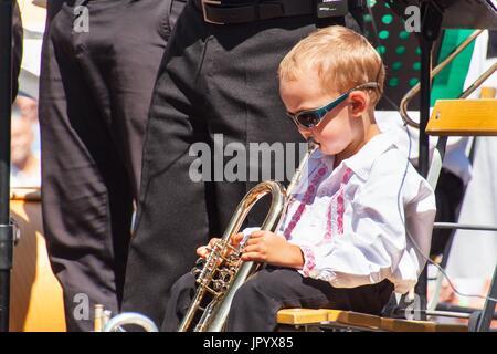 Buchlovice, Czech Republic, July 29, 2017: Little boy plays trumpet at folk festivities. Gifted child. Traditional - Stock Photo