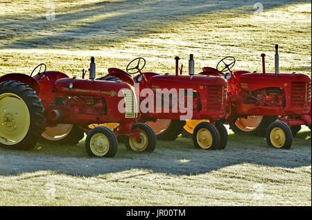 Three red farm tractors in a line on a farm field with an early morning frost in New Brunswick Canada - Stock Photo
