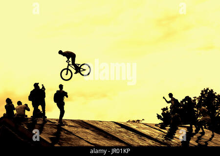Extrem Sport and risk. Performance at competitions. Silhouette of unidentified young man performs stunts on background - Stock Photo
