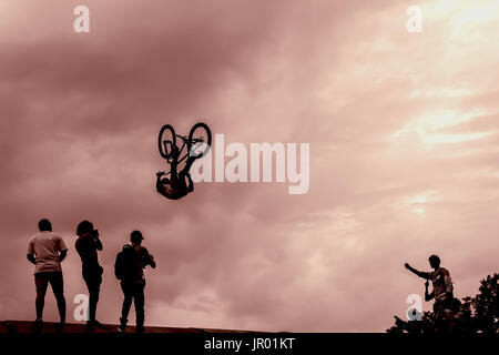 Extrem Sport and risk. Performance at competitions. Silhouette of unidentified young man performs stunts on the - Stock Photo