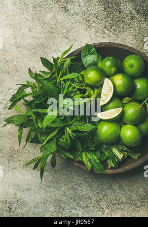 Flatlay of freshly picked organic limes and mint leaves for making cocktail or lemonade in wooden plate over grey - Stock Photo