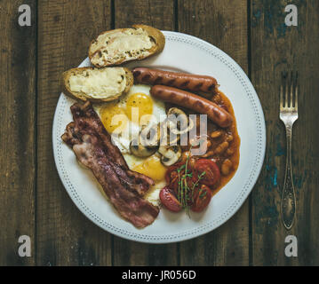 Flat-lay of traditional English breakfast with fried eggs, sausages, mushrooms, sauted tomatoes, bacon, beans and - Stock Photo