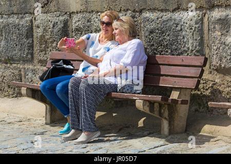 Two women sitting on bench taking selfie at Lyme Regis, Dorset in July - Stock Photo